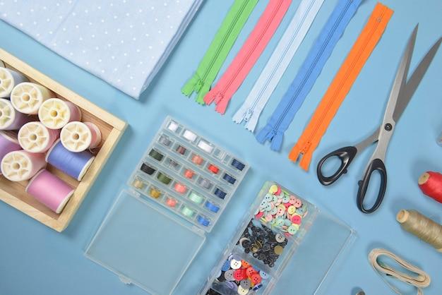 Flat lay de material de costura contém os tecidos, tesouras, zíperes e rolos de linha.