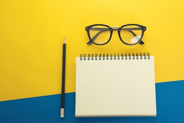 Flat lay design de caderno em branco sobre fundo amarelo