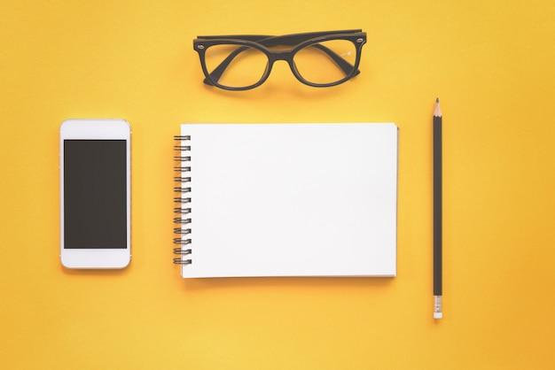 Flat lay design de mesa de trabalho com notebook, óculos, lápis e smartphone