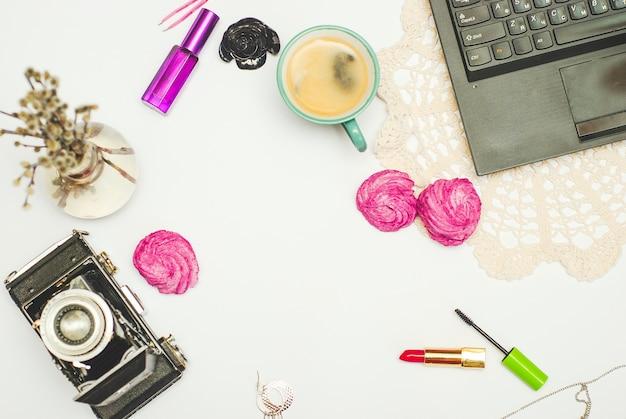 Flat lay-desk com café, zephyr, laptop, câmera vintage e cosméticos