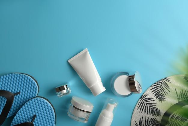 Flat lay, espaço de trabalho vista superior com chapéu, protetor solar no fundo azul. conceito de blogueiro de viajante elegante de verão.