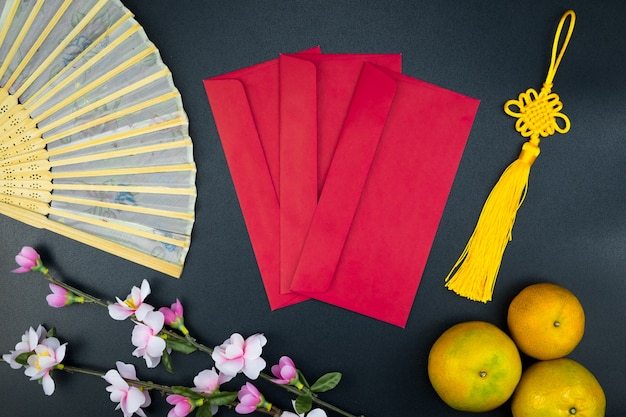 Flat lay holiday of chinese new year pacote vermelho e de acessórios flor no topo