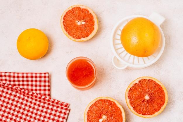 Flat lay juicer ao lado de toranjas cortadas ao meio
