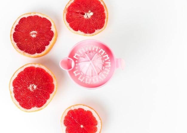 Flat lay juicer e grapefruit em metades