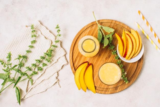Flat lay lindo arranjo com smoothies de manga e plantas