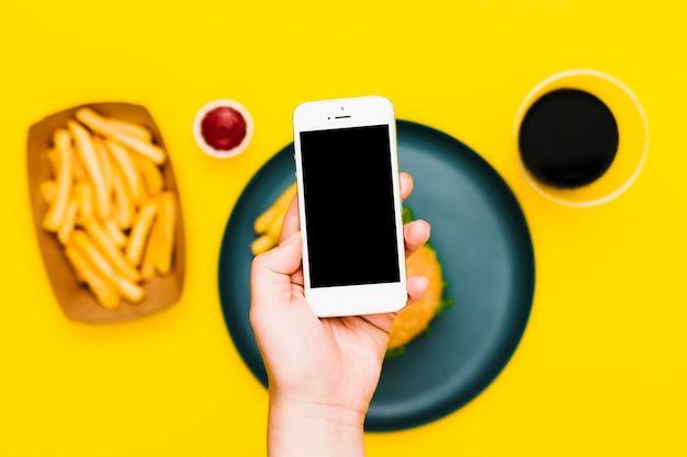 Flat-lay mão segurando o smartphone sobre o prato com hambúrguer e batatas fritas