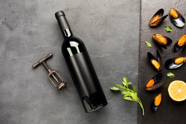 Flat-lay mexilhões cozidos em ardósia com garrafa de vinho