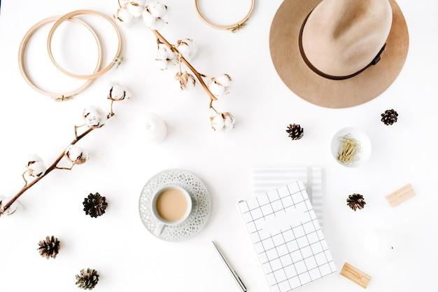 Flat lay moderno criativo arranjo de acessórios femininos com café, galho de algodão e diário. chapéu, galho de algodão, caderno, xícara de café, cone de abeto, clipes dourados em branco
