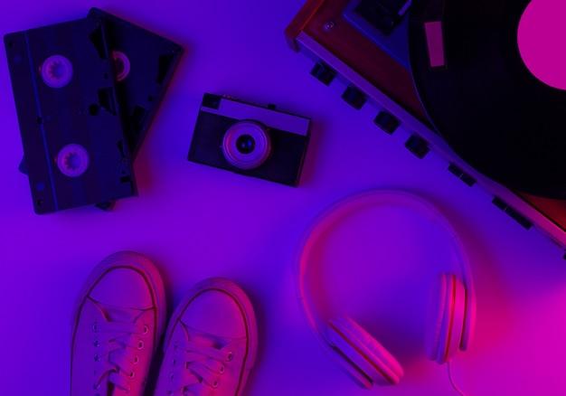 Flat lay retro cultura pop dos anos 80 objetos vinil player fones de ouvido fitas de vídeo tênis câmera de filme