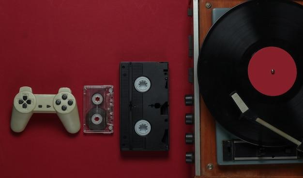 Flat lay retro mídia e entretenimento. vitrola de vinil com disco de vinil, câmera de filme, videocassete, fita cassete, gamepad em fundo vermelho anos 80. vista do topo