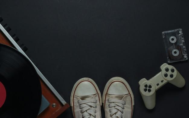 Flat lay retro mídia e entretenimento. vitrola de vinil com disco de vinil, fita cassete, gamepad, tênis em um fundo preto. copie o espaço. anos 80. vista do topo