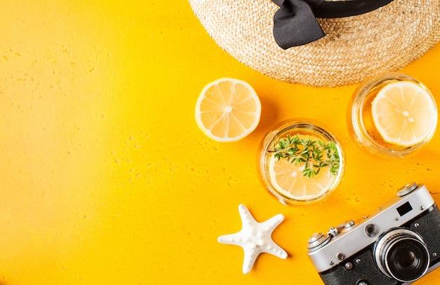 Flat lay verão limonada chapéu de palha câmera estrela do mar em amarelo