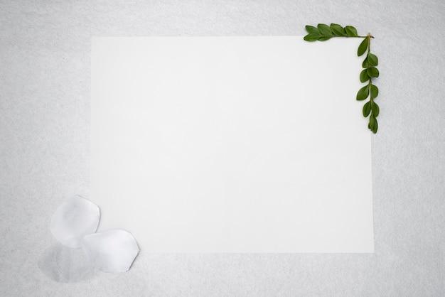 Flat lay white cartão de casamento com pétalas