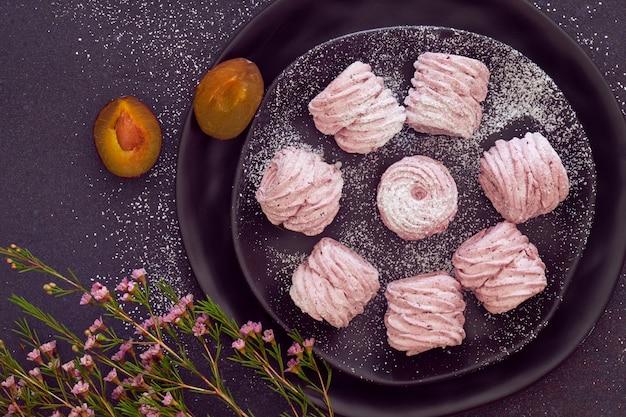 Flat leigos com um prato de marshmallows caseiros (zephyr, merengue) feitos com ameixas pretas