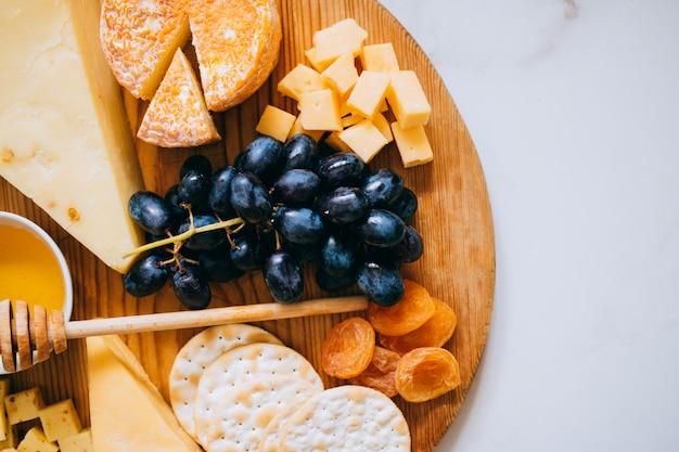 Flat leigos com vários tipos de queijo, uvas, nozes, mel e bolacha na placa de madeira em mármore