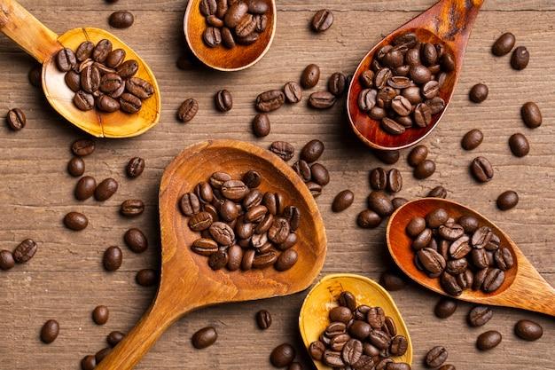 Flat leigos grãos de café em colheres de madeira