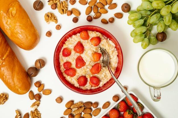 Flat leiteria mingau com frutas e nozes arranjo no fundo liso