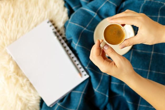 Flatlay aconchegante com bandeja de madeira, mãos segurando uma xícara de café, vela, caderno em lençóis brancos macios e cobertor azul. trabalhe no conceito de casa. vista do topo.