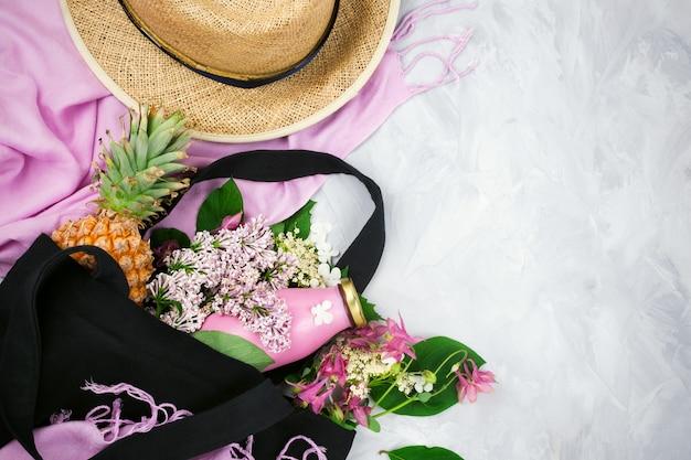 Flatlay bonito com ecobag preto com flores silvestres e lilás, garrafa de suco, abacaxi, cachecol rosa e chapéu de palha em fundo cinza cimento com copyspace