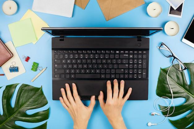 Flatlay bonito com mãos de mulher imprimindo, um laptop, telefone celular, óculos, folhas de filodendro e outros acessórios de negócios. postura plana.