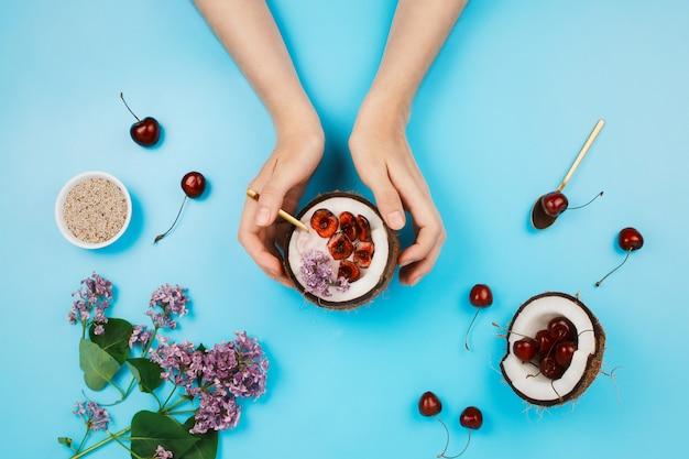 Flatlay com a mão de uma mulher segurando metade do coco com uma tigela de iogurte à base de plantas com sementes frescas de cereja e chia no lado sobre fundo azul