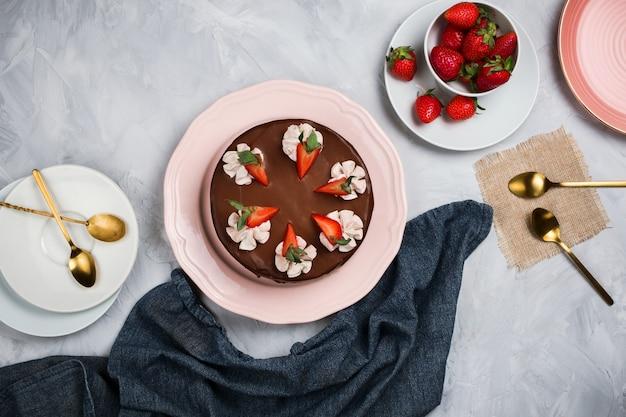 Flatlay com bolo de chocolate vegan, morangos e pratos vazios com colheres de ouro sobre fundo de cimento com copyspace