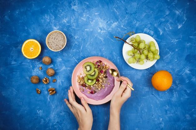 Flatlay com café da manhã vegetariano saudável de iogurte à base de plantas de baga com granola, sementes de chia, várias frutas e nozes sobre fundo azul