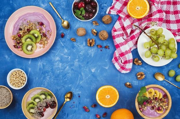 Flatlay com café da manhã vegetariano saudável de tigelas de iogurte à base de plantas de baga com granola, sementes de chia, várias frutas e nozes sobre fundo azul com copyspace
