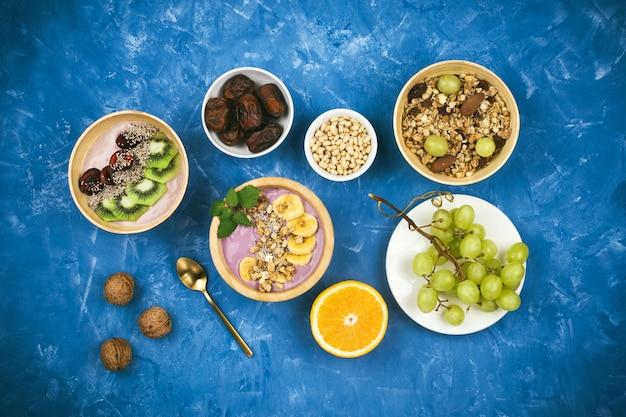 Flatlay com café da manhã vegetariano saudável de tigelas de iogurte à base de plantas de baga com granola, sementes de chia, várias frutas e nozes sobre fundo azul