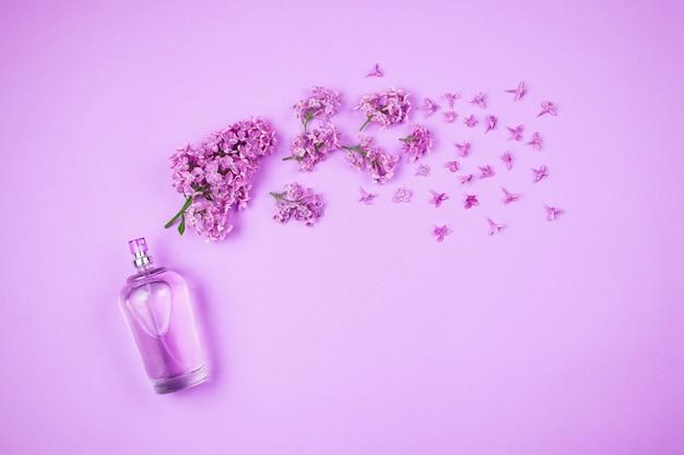 Flatlay com flores lilás violetas e frasco de perfume