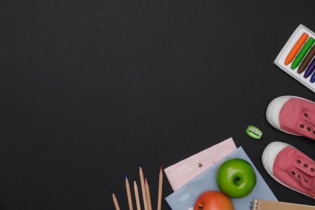 Flatlay criativo da mesa de educação verde com livros de estudante, sapatos, espaço vazio colorido lápis no fundo do quadro-negro, conceito de educação e volta às aulas