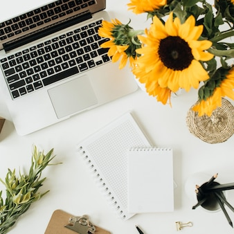 Flatlay da área de trabalho da mesa do escritório em casa com laptop, notebook, buquê de girassóis amarelos em branco