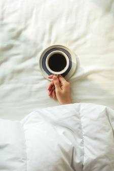 Flatlay da mão de uma mulher coberta por um cobertor segurando a xícara de café preto em uma cama