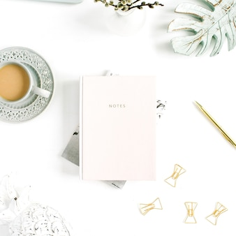 Flatlay da mesa da secretária do escritório em casa. espaço de trabalho com caderno rosa pastel pálido e decorações em fundo branco. camada plana, vista superior