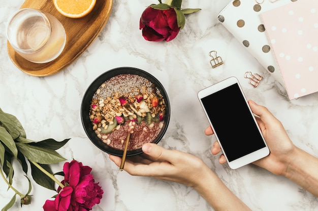 Flatlay das mãos da mulher com notebook e telefone, tigela de batido vegano com pudim de chia coberto com granola, kiwi, pinhões e botões de rosa e flores de peão em mármore, conceito de café da manhã saudável