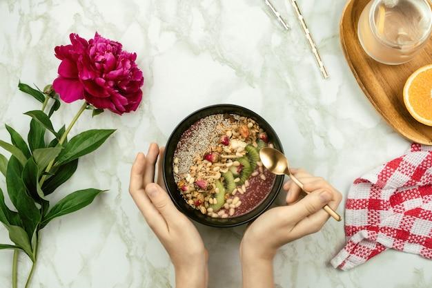 Flatlay das mãos da mulher segurando a tigela de batido vegan com pudim de chia coberto com granola, kiwi, pinhões e botões de rosa com flor de peônia, água com limão e colher na mesa de mármore
