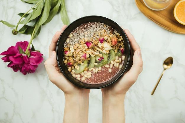 Flatlay das mãos da mulher segurando a tigela de batido vegan com pudim de chia coberto com granola, kiwi, pinhões e botões de rosa com flor de peônia e colher na mesa de mármore
