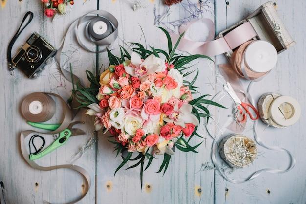 Flatlay de bouquet de casamento de laranja e fitas na mesa de trabalho
