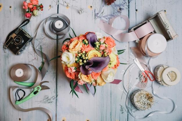 Flatlay de bouquet de casamento, fitas e câmera