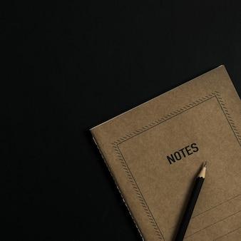 Flatlay de caderno de folha de papel ofício, lápis, clipes em preto