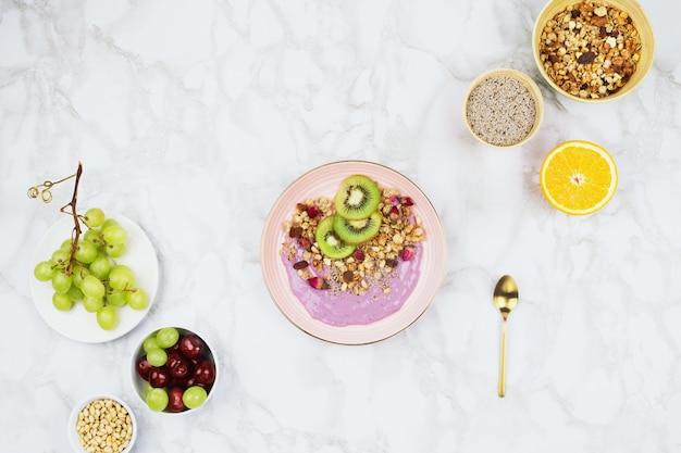 Flatlay de café da manhã vegano com iogurte à base de plantas coberto com fatias de kiwi, granola, sementes de chia e várias frutas no fundo de mármore
