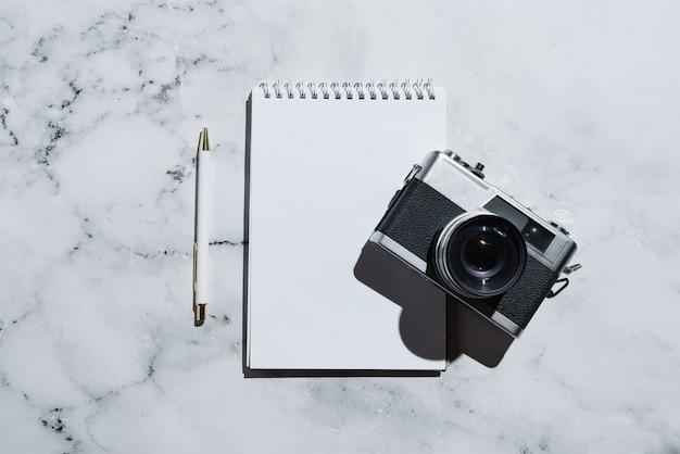 Flatlay de câmera de filme vintage e notebook com caneta em mármore