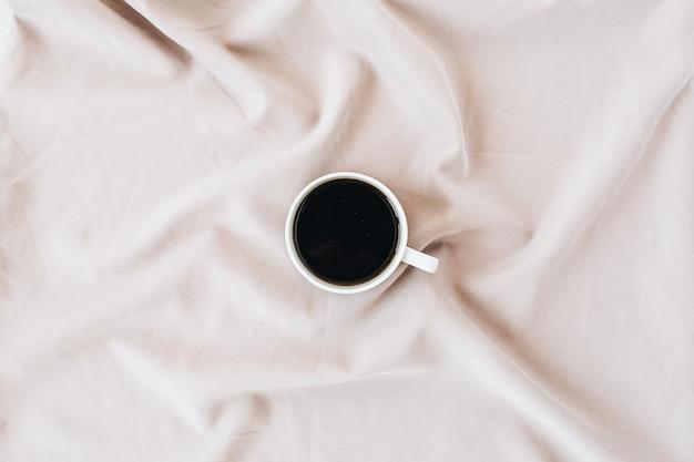 Flatlay de caneca de café preta em cobertor rosa pastel