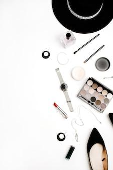 Flatlay de cosméticos e acessórios de moda feminina. chapéu, sapatos, paleta, batom, relógios, pó sobre fundo branco