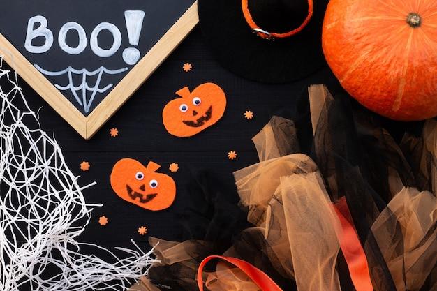 Flatlay de halloween laranja e preto. inscrição de giz boo, abóboras de feltro, tule, teia de aranha em um fundo preto.