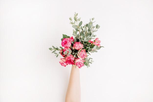 Flatlay de mão feminina segura flores rosas e buquê de eucalipto. camada plana, vista superior