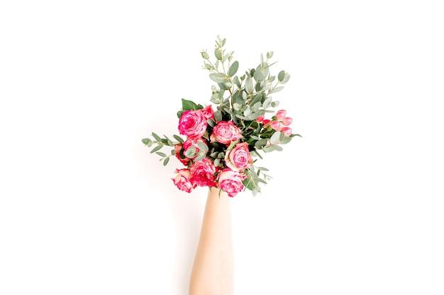Flatlay de mão feminina segura flores rosas e buquê de eucalipto em fundo branco. camada plana, vista superior