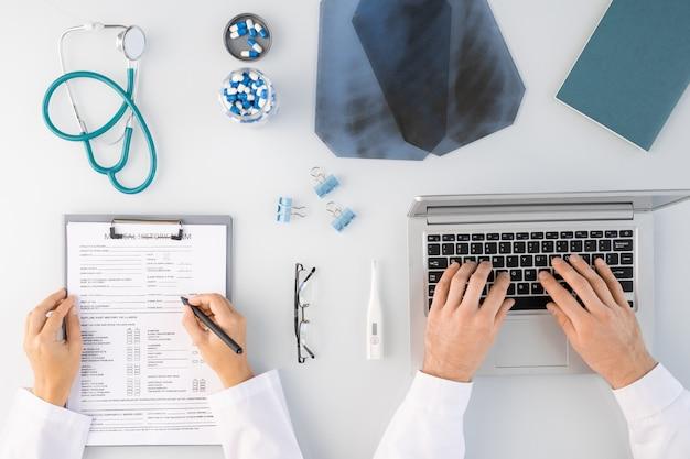 Flatlay de mãos de dois médicos fazendo anotações médicas e digitando em um laptop cercado por imagens de raio-x, pílulas, estetoscópio e outros