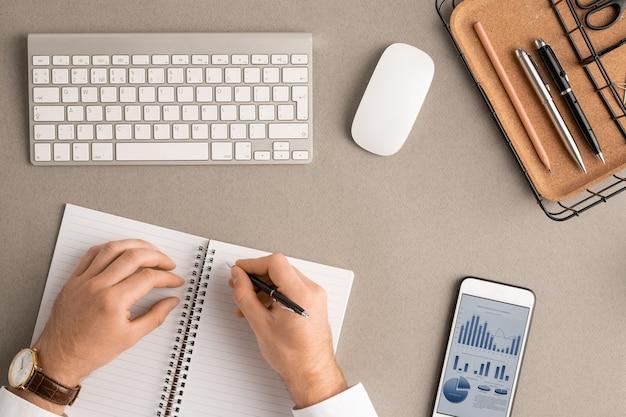 Flatlay de mãos de jovem corretor com caneta sobre a página em branco do caderno aberto, fazendo anotações entre material de escritório, mouse, gadget e teclado