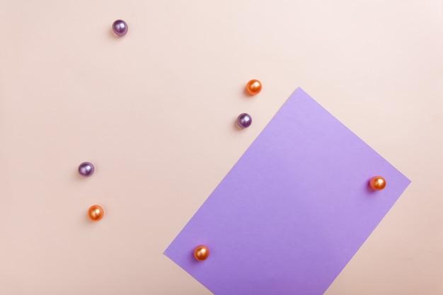 Flatlay de papel violeta e bolas de cor em fundo rosa pálido. lugar para o seu texto. copyspace.